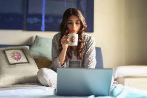 Mulher tomando café e fazendo Terapia Online pelo seu notebook