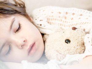 criança dormindo com um ursinho
